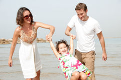 Father and mother hold the daughter. Young couple embracing and enjoying with young daughter on the beach stock photo