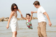 Father and mother hold the daughter. Young couple embracing and enjoying with young daughter on the beach royalty free stock photos
