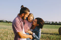 Father and mother hug her little daughter outdoors in field Royalty Free Stock Image