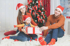 Father, mother and infant holding Cristmas gift near Christmas tree Stock Photos