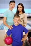 Father and mother keep son in bowling clubb Stock Images