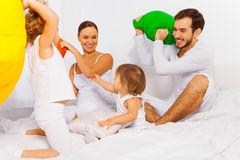 Father, mother and kids play with colorful pillows Royalty Free Stock Photo