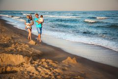 Father, mother and kids walking along the beach, near the ocean, happy lifestyle family concept.  royalty free stock photos