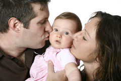 Father and mother kissing baby Royalty Free Stock Images
