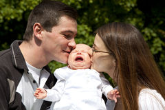 Father and mother kissing their daughter Royalty Free Stock Image