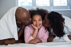 Father and mother kissing their daughter on bed Stock Images