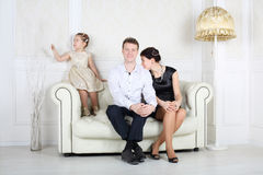 Father, mother and little cute daughter sit at sofa Royalty Free Stock Images