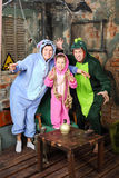 Father, mother and little daughter in costumes of dragons. Father, mother and little daughter in colorful costumes of dragons attack in very old room royalty free stock photo