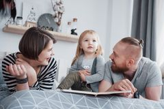 Father, Mother and Little Daughter Reading Children`s Book on a Sofa in the Living Room. Happy big family read an Stock Photo