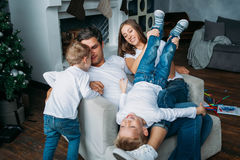 Father and mother lying on the sofa and playing with two little sons Royalty Free Stock Photo