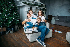 Father and mother lying on the sofa and playing with two little sons Royalty Free Stock Photography