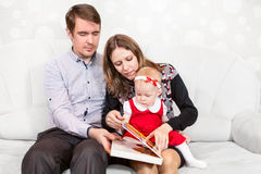 Father and mother opening book for baby reading Royalty Free Stock Photo