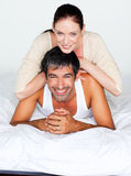 Father and mother playing in bed Stock Photo