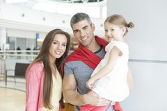 Father and mother pose with young daughter in shopping mall Royalty Free Stock Photography