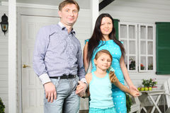 Father, mother and pretty daughter stand next to house Royalty Free Stock Photos