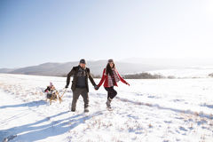 Father and mother pulling daughter on sledge, running. Winter na. Mother and father pulling daughter on sledge, running. Beautiful family in sunny winter nature Royalty Free Stock Images