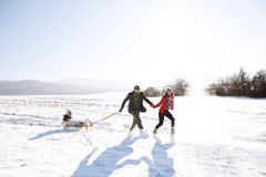 Father and mother pulling daughter on sledge, running. Winter na Royalty Free Stock Photos