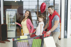 Father and mother push young daughter in shopping trolley through mall Royalty Free Stock Photography