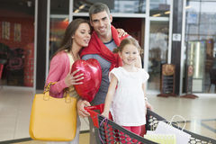 Father and mother push young daughter in shopping trolley through mall Royalty Free Stock Photo