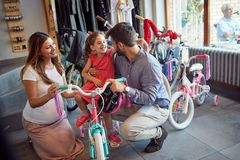.father and mother shopping new bicycle for little girl in bike shop. Father and mother shopping new bicycle for happy little girl in bike shop royalty free stock images
