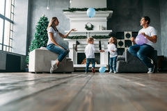 Father and mother siting on sofa playing air balloons with two little sons. At home living room Royalty Free Stock Image