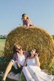 Father and mother sitting under a haystack, and their daughter sitting on a haystack Stock Photos