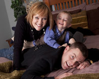 Father, mother and son. Young blonde boy playing with his mother and father on a bed royalty free stock photos