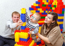 Father, mother and son build tower from bricks together Royalty Free Stock Photos