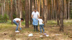 Father, mother and son collect garbage in a bag in the forest or Park. Education of children`s attitude to nature