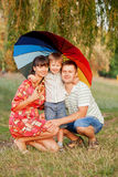 Father, mother and son with colorful umbrella. Stock Image