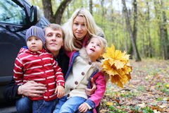 Father, mother, son and daughter with maple leaves. Happy father, mother, little son and daughter with yellow maple leaves near car in autumn forest. Focus on stock image