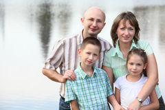Father, mother, son and daughter on pond backgroun Stock Image