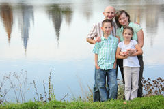 Father, mother, son and daughter staying near pond Stock Photography