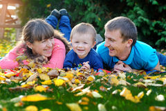 Father, mother and son happy family on a green lawn in the fall Stock Photography