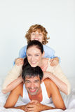 Father, mother and son playing in bed Stock Image
