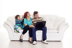 Father, mother and son sitting on the sofa with notebook Royalty Free Stock Images