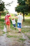 Father, mother and son walking outdoors. Royalty Free Stock Photo