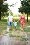 Father, mother and son walking outdoors. Stock Image