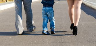 Father, mother and son walking in an urban neighborhood. Family feet and legs in jeans. Father, mother and son walking in an urban neighborhood. Rear view Stock Photography