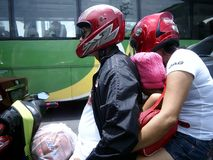 A father and mother with their child ride a motorcycle. Royalty Free Stock Images