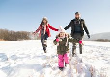 Father and mother with their daughter, playing in the snow. Father and mother having fun with their daughter, playing in the snow. Sunny white winter nature royalty free stock images