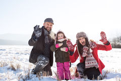 Father and mother with their daughter, playing in the snow. Father and mother having fun with their daughter, playing in the snow, waving. Sunny white winter Royalty Free Stock Photography