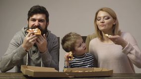Father, mother and their little son eat delicious pizza isolated on white background. Family enjoys a delicious pizza. Parents and child sitting on wooden stock video footage