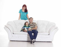 Father, mother and their son sitting on the sofa Stock Images