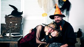 Father, mother and their son in suits of witches, sorceress and skeletons are hugging on a Halloween holiday. Halloween. Party and celebration concept. Family stock footage