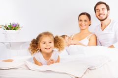 Father, mother and two kids laying on white bed Stock Photos