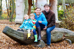 Father, mother and two little kids sitting on a bench in autumn Stock Photography