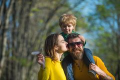 Father and mother walk with son, family love. Family love is in autumn park outdoor. Carefree time together.  royalty free stock photography