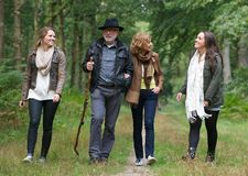 Father and mother walking with daughters in the woods. Portrait of a father and mother walking with daughters in the woods Royalty Free Stock Images