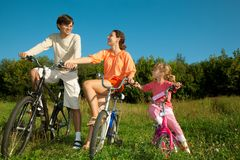 Father, mum and daughter on bicycles in park Royalty Free Stock Photos